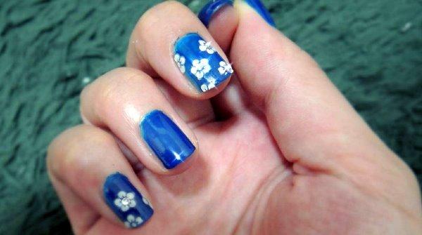 Синий маникюр с белыми цветами.